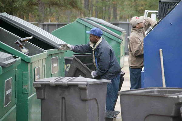 Two men doing recycling work on trash cans