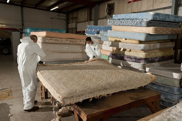 Two workers recycling mattresses, stack of old mattresses in the background