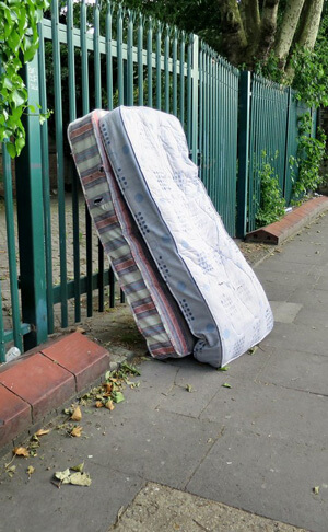 Mattress, placed against a fence outside