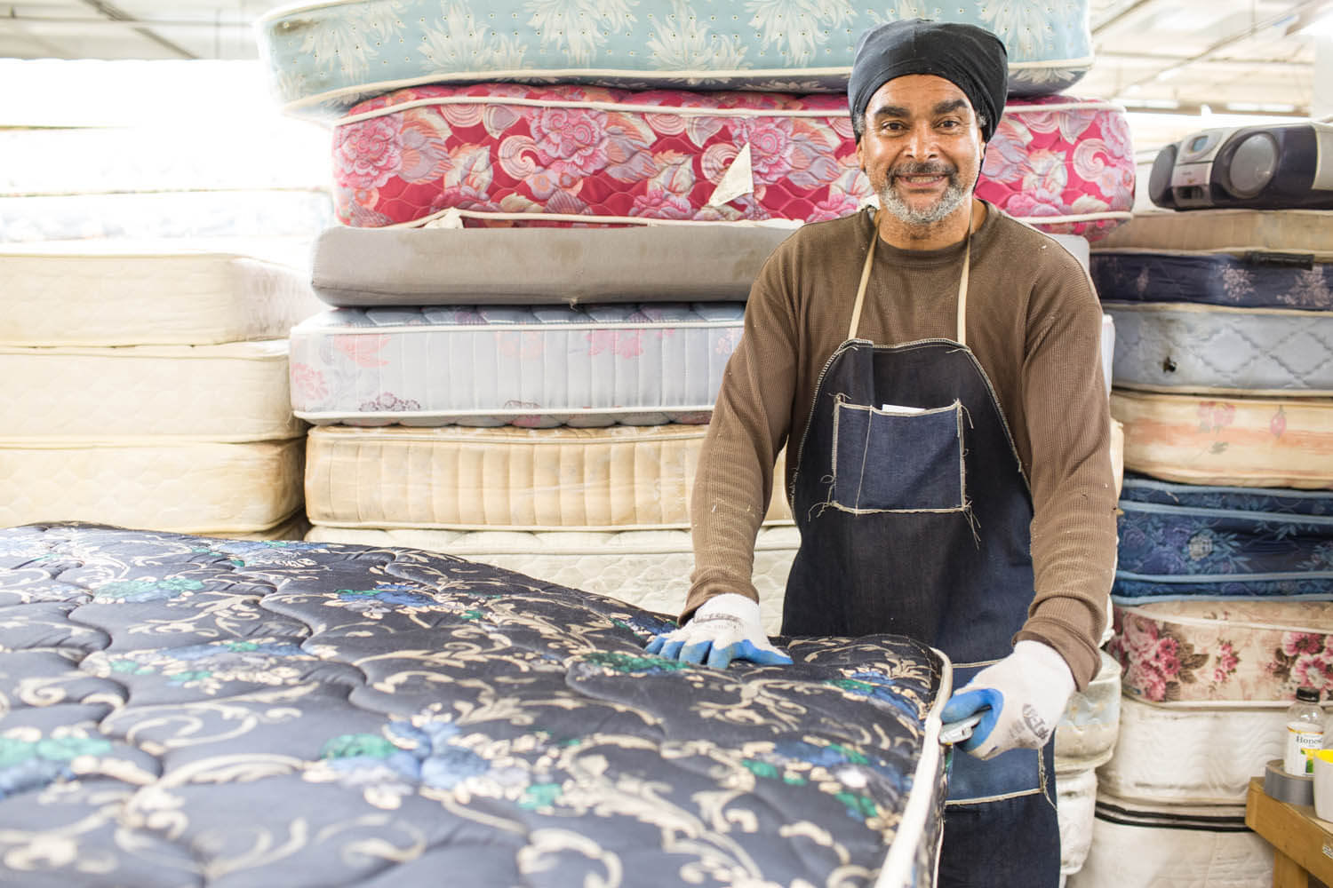 Man in work clothes recycling mattresses