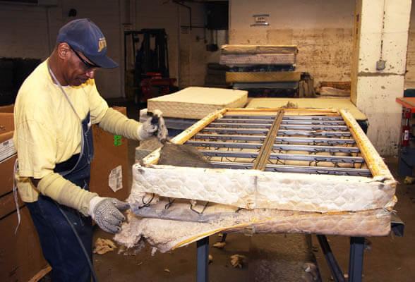 Man deconstructing a mattress